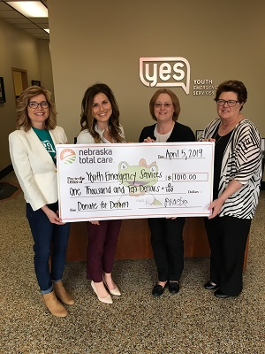 employees present a giant check to agency